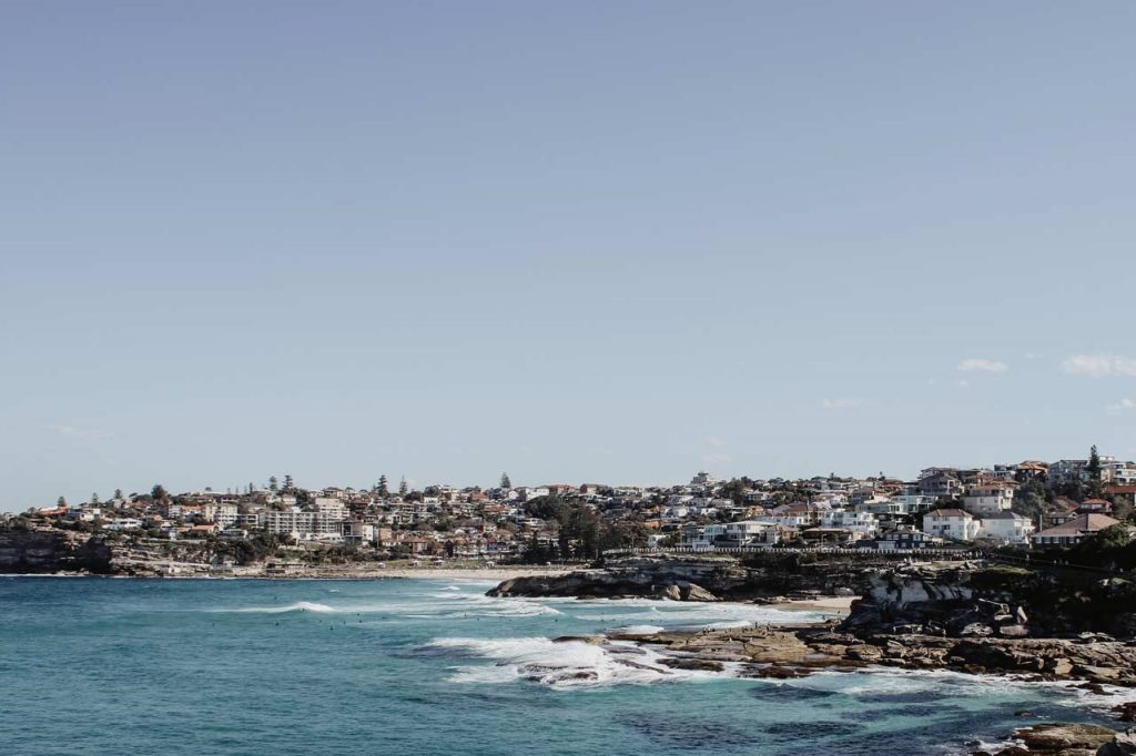 Image of Bronte Beach and surrounding area. Blue skies, Bronte houses & buildings & businesses, Bronte beach with waves crashing on the rocks