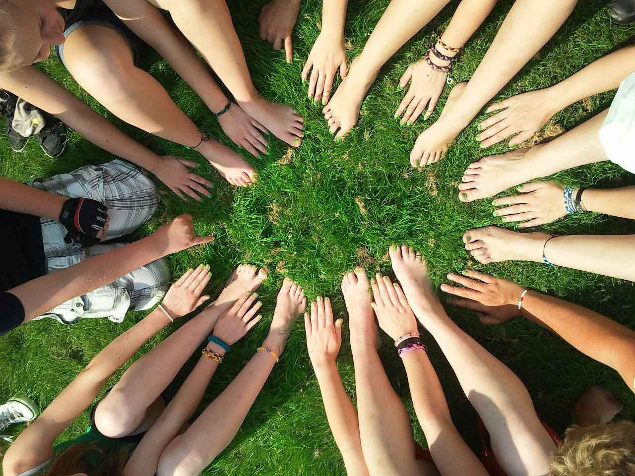 A birds-eye view of a circle of people placing their hand & feet into the middle to demonstrate togetherness. One of the key factors in small businesses helping local communities.