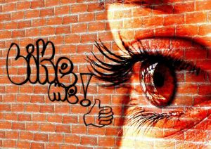 A large red brick wall with a superimposed female face showing the right eye and eyebrow and long eyelashes. On the wall is also some grafitti writing of the words like me with a representation of a Facebook like thumbs up. showing how cost effective marketing can be impressive for small business.