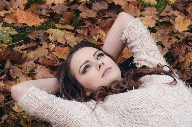 A woman lying down on fallen leaves, with her hands behind her head staring thoughtfully up at the sky. Take some time to think and analyse your website and social media traffic