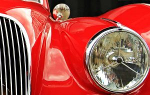A close up image of an old Jaguar sports car viewing the fron headlight and a portion of the front radiator grill. The car body is painted in a luxurious red and is highly polished, waxed and shiny.