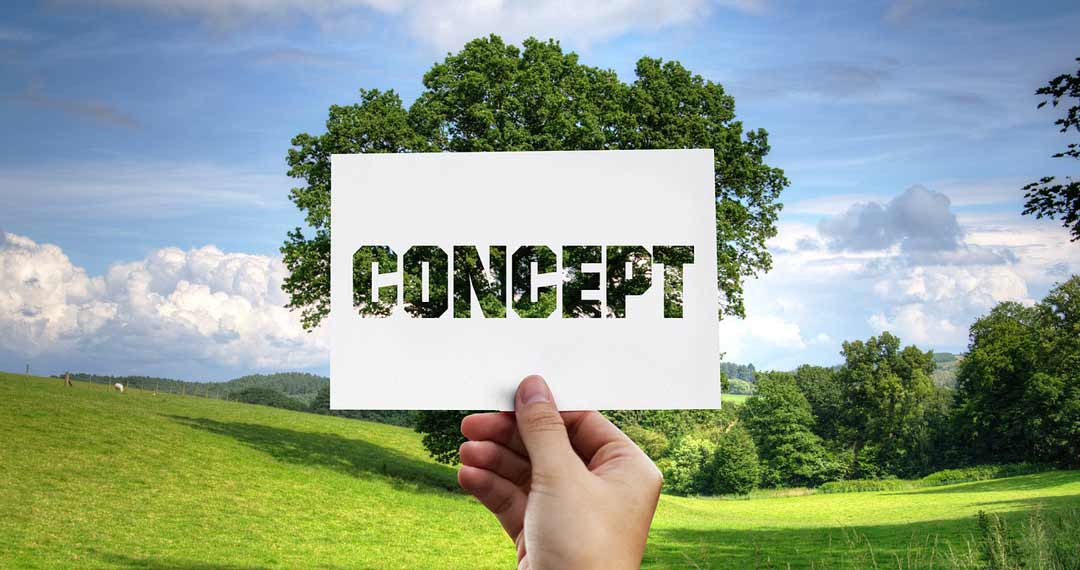 An image of green rolling pastures, with a large tree in the centre. The tree is covered by a white piece of card held up in front with the word concept cut out of the card to enable the trees leaves to be the background of the word. Small business marketing concepts are important to enable your target audience to see your business and your services & products.