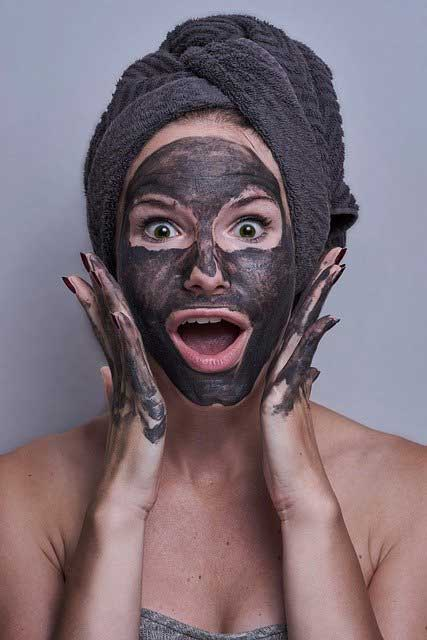 A woman with a brown face pack on her face, and a towel wrapped around her head. her hands are stretched out either side of her face and she has an opened mouth wide eyed look of surprise on her face.