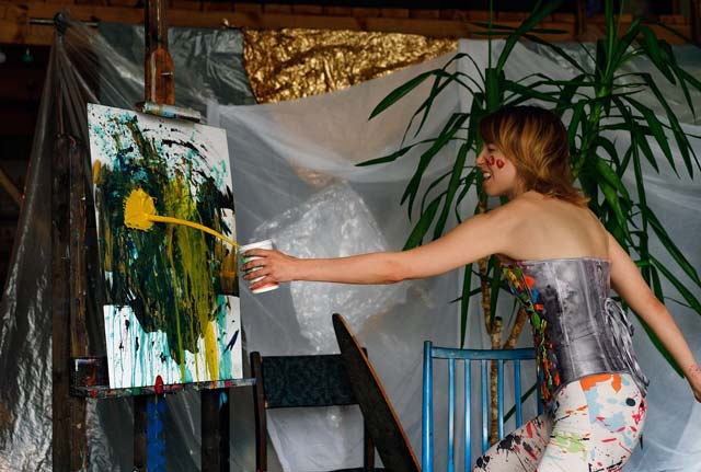 A female artist throwing yellow paint onto a canvas on an easel. the paint is making a splash on the canvas as the paint leaves a cup being held by the woman at arms length as she throws.