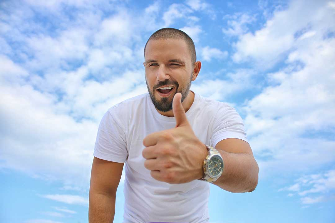Customer reviews and Local SEO & how they can help your small business. A young man in a white t-shirt giving a thumbs up signal and with a wink and a smile dep[icting how important it is to get feedback from your customers to help your local seo
