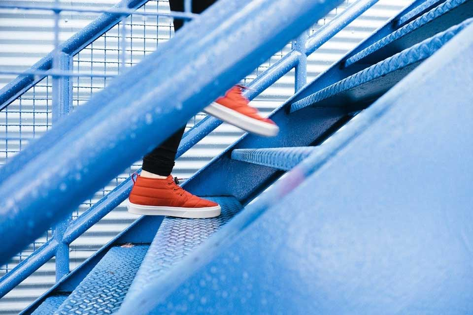showing steel stairs with the legs and feet of a woman running up the steps in black leggings and orange joggers. depicting the step by step approach to improving your search engine ranking one step at a time