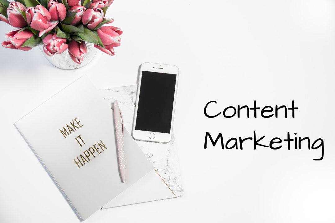 Image above a desk, with a bowl of tulips, a mobile phone, a card with the words make it happen and title text displaying content marketing